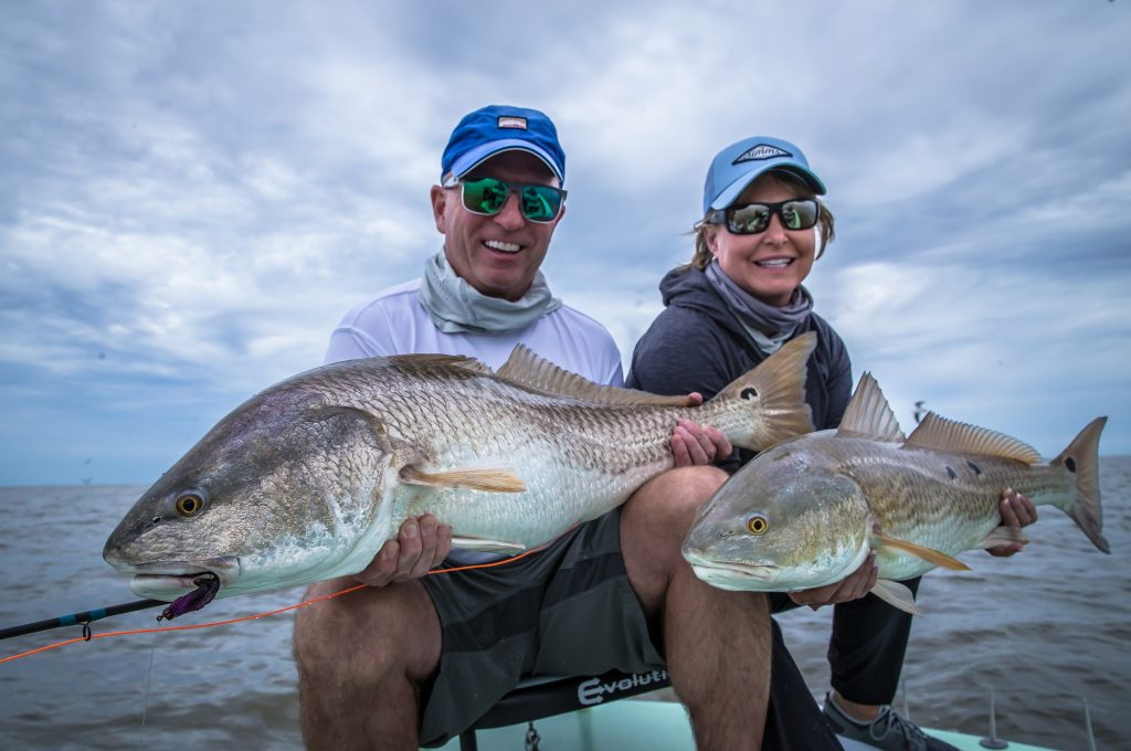 A couple who booked a trip getting a double header red fish action
